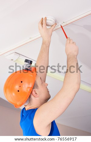 Technician in hard hat working at the fire sensor - stock photo