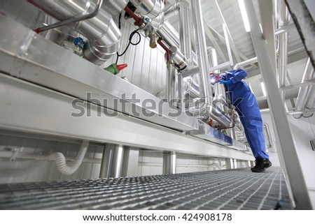 Technician in mask,gloves,goggles and blue uniform controlling technological system - stock photo