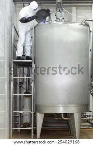 Technician in protective coveralls  controlling industrial process in factory - stock photo