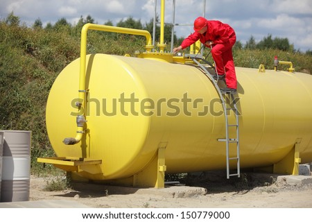 technician in red uniform working on large fuel tank  - stock photo