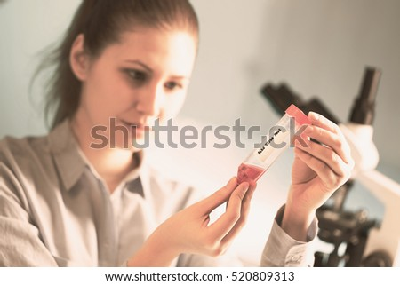 technician in the laboratory with a pipette and test tube. Toned Image