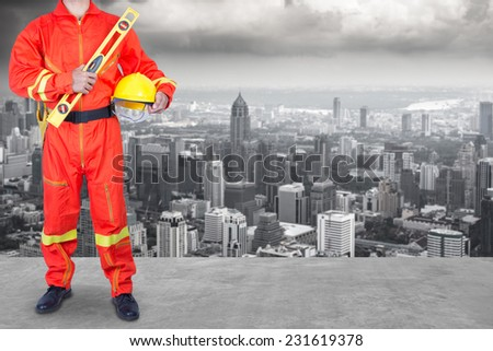 technician in uniform working at high building construction site against urban scene balcony over looking city dusky before rain falling - stock photo