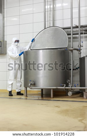 technician in white protective uniform,mask,goggles,gloves  opening large industrial process tank in factory - stock photo