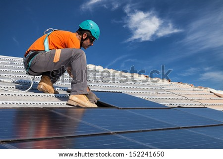 technician install new generation photovoltaic solar panels on roof - stock photo