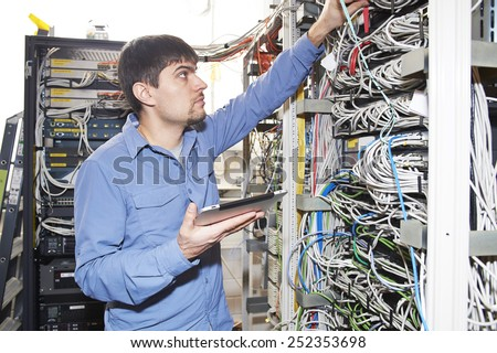 Technician is checking server wires in data center using tablet