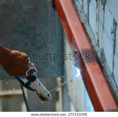 Technician is using steel welding sparks during welding work. - stock photo