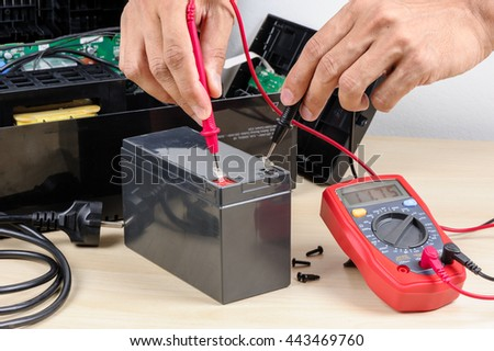 Technician measuring the voltage of battery for UPS (Uninterruptible Power Supply) with multimeter. - stock photo