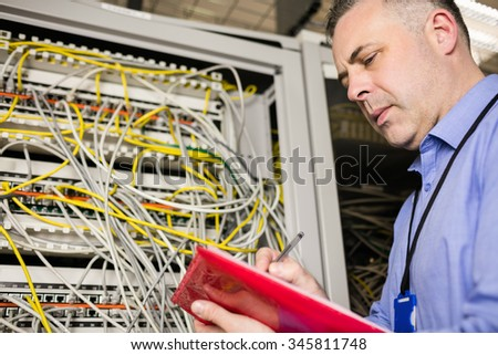 Technician noting issue on clipboard at the data centre