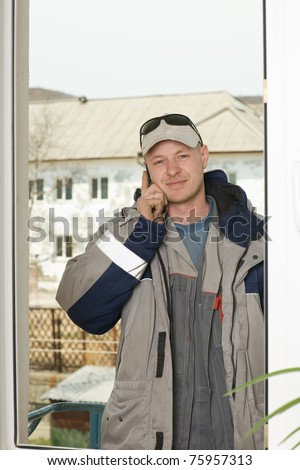 Technician of the air conditioning system using a mobile phone while on the lift aerial platform outside the window. Work on installing a new air conditioner. - stock photo