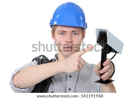 Technician pointing to CCTV camera - stock photo