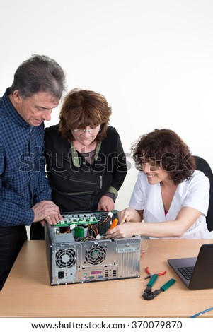 Technician repairing a computer and a senior couple is waiting for