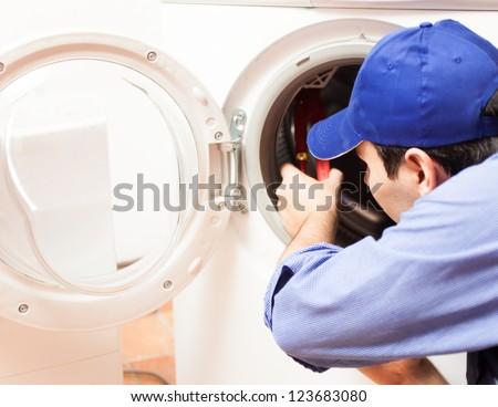 Technician repairing a washing machine - stock photo
