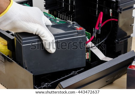 Technician replacing the UPS(Uninterruptible Power Supply) battery.