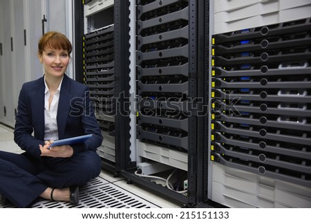 Technician sitting on floor beside server tower using tablet pc in large data center