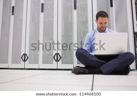 Technician sitting on floor working on laptop in data center