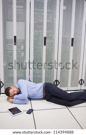 Technician sleeping in front of servers in data  center - stock photo