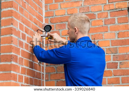 Technician Standing On Ladder Installing Camera On Wall - stock photo