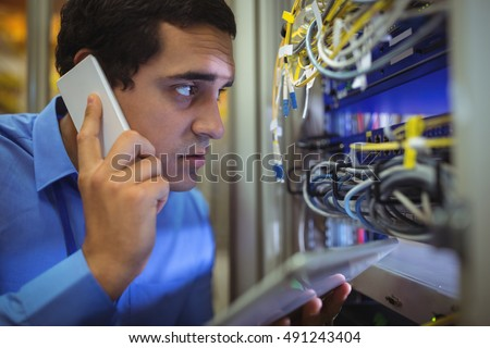 Technician talking on mobile phone while analyzing server in server room