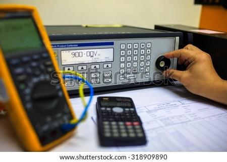 Technician turn switch of  precision multi calibrator for calibration multimeter  - stock photo
