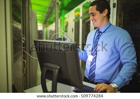 Technician using digital cable analyzer while working on personal computer in server room