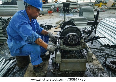 technician using machine tapping a steel pipe for joint connection sprinkle system