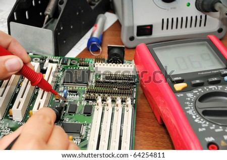 Technician with multimeter probes at his work place with soldering iron, multimeter and circuit board - stock photo