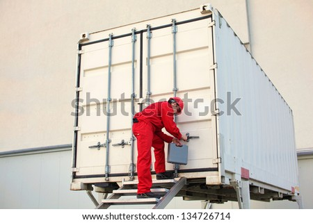 technician with tool case opening movable workshop in container - stock photo