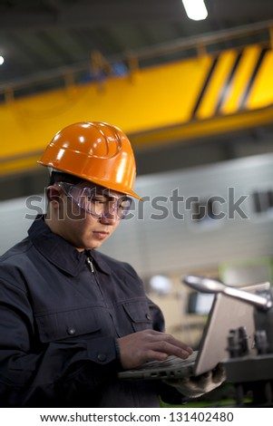 Technician working in factory using laptop - stock photo