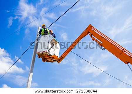 Technician works in a bucket high up on a power pole. - stock photo