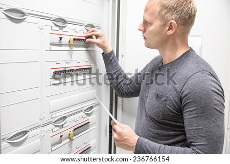 Technician works in large electric fuse cabinet - stock photo