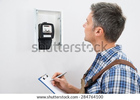 Technician Writing Reading Of Meter On Clipboard