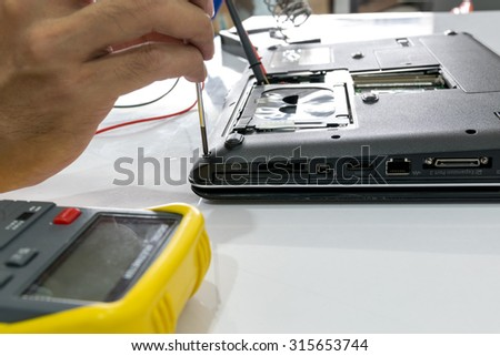 Technicians are repairing a notebook. - stock photo