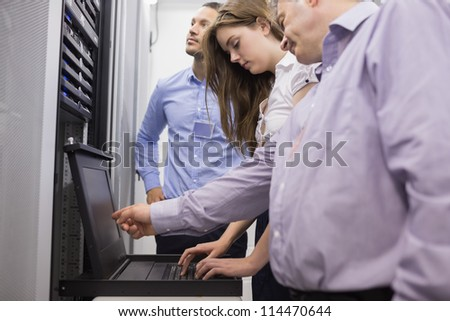 Technicians checking servers with laptop in data center - stock photo