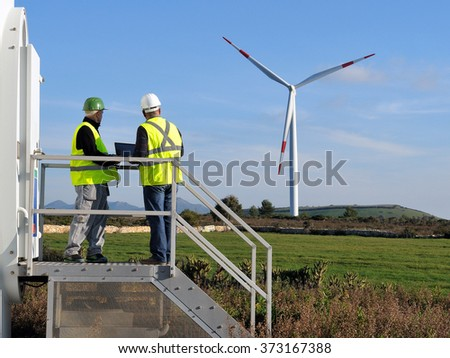 Technicians engaged in the detecting of a wind turbine installation for the production of energy - stock photo