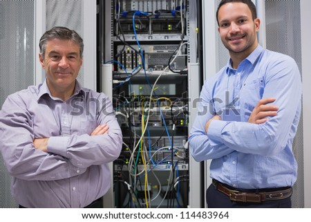 Technicians smiling while standing in front of servers in data center - stock photo