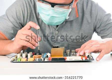 Technological background with closeup on tester checking motherboard. Electronics repair service, hands of female tech fixes an electronic circuit,computer technology concept - stock photo