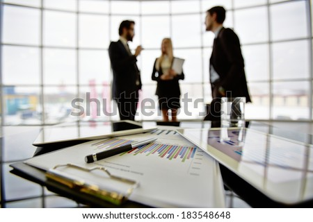 Technological devices and financial document at workplace on background of three business partners discussing ideas - stock photo