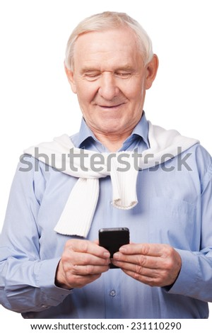 Technological wonders of nowadays. Happy senior man holding mobile phone while standing against white background  - stock photo