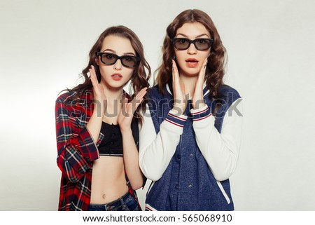 technologies, emotions, lifestyle, people, teens and friendship concept - Two attractive smiling girl in a 3d-glasses slightly tilted to the right. Isolated on white background