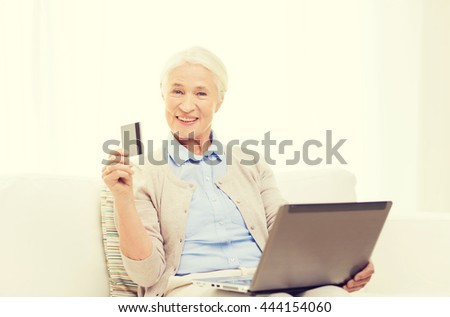 technology, age and people concept - happy senior woman with laptop compute and credit or bank card r at home - stock photo