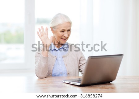 technology, age, gesture, communication and people concept - happy senior woman with laptop computer having video chat at home and waving hand - stock photo