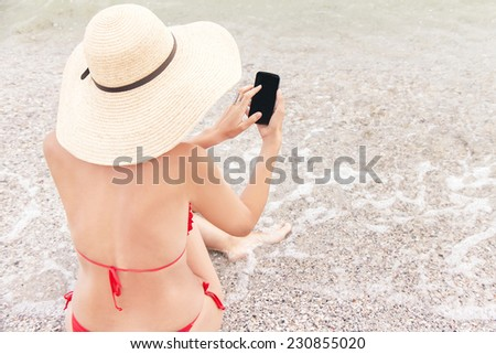 Technology and beach concept. Caucasian resting woman on vacation is sitting on the beach with sea and using a smart phone (mobile). Relaxing female model in red bikini and hat.  - stock photo