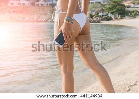 Technology and beach concept.  resting woman on vacation is sitting on the beach with sea and using a smart phone (intentional sun glare) - stock photo