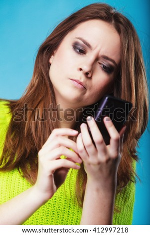 Technology and communication. Confused woman teenage girl texting on mobile phone, using smartphone reading sms message on blue - stock photo