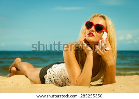 Technology and communication. Young woman teen girl talking on mobile cell phone using smartphone on beach