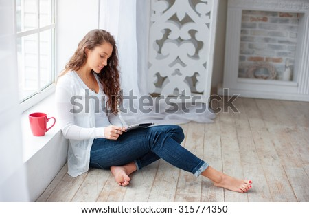 Technology and coziness. Beautiful young woman with cup of tea using tablet computer while sitting on floor at home. - stock photo