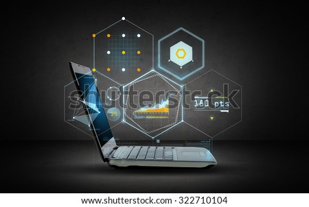 technology and future concept - open laptop computer with virtual chart projection over dark gray background - stock photo