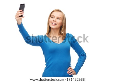technology and internet concept - smiling woman taking self picture with smartphone camera - stock photo
