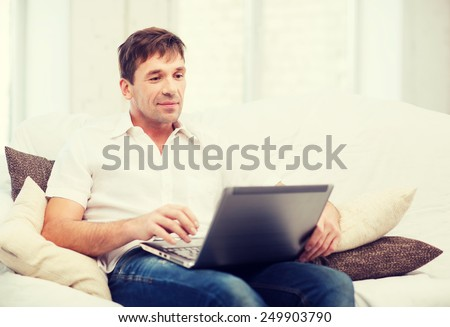 technology and lifestyle concept - man working with laptop at home - stock photo