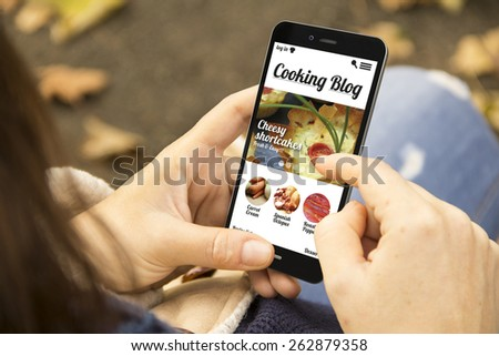 technology and lifestyle concept: young woman with cooking blog on the screen phone at the park - stock photo